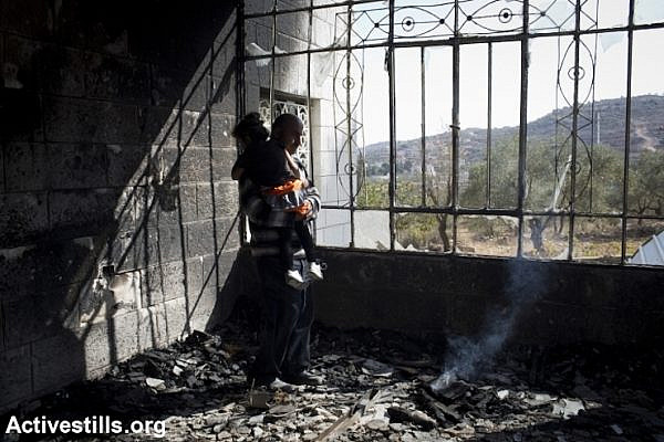 Khaled Abed a-Rahman Dar Khalil inspects the damage inside his home, which was torched by Jewish settlers, Sinjil, West Bank, November 14, 2013. Five children were treated for smoke inhalation. (Photo: Oren Ziv/Activestills.org)