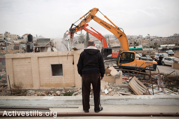 Israeli authorities demolish the Adgluni family home in East Jerusalem, January 27, 2014. (Tali Mayer/Activestills.org) Authorities claim the house was built on lands that do not belong to the family.