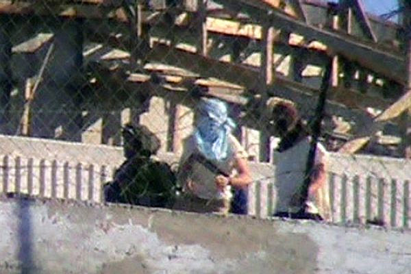 IDF soldier escorting masked settlers as they attack the Palestinian village of Urif, January 6, 2014. (Screenshot of video by Osama Safdi/B'Tselem)
