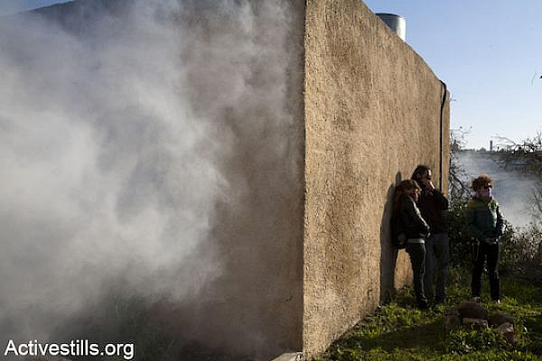 Israeli activists seek fresh air amid clouds of tear gas at the weekly demonstration in Nabi Saleh, January 6, 2012. (Photo: Keren Manor/Activestills.org)