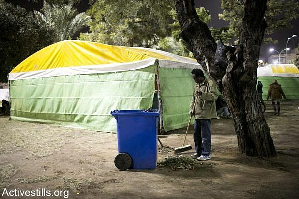 An African asylum seeker cleans the area outside tents for homeless refugees in Levinsky park, south Tel Aviv, December 20, 2012. The Tel Aviv municipality, along with several NGOs, set up two tents as a temporary winter shelter for homeless refugees in the park. (photo: Activestills.org)