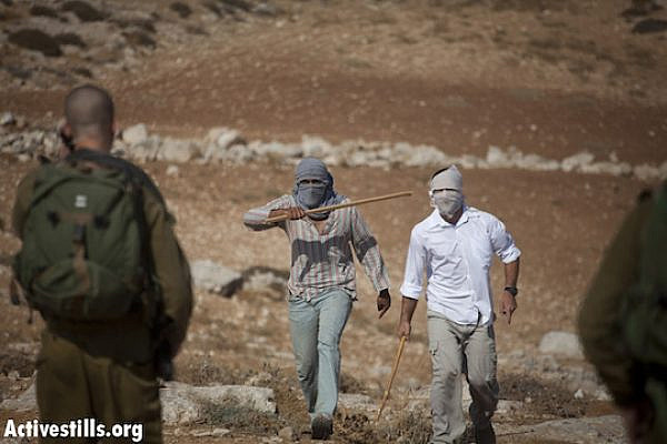 File photo of settlers threatening Israeli activists and Palestinians with sticks in front of the Ma´on settlement, South Hebron hills. (Photo by: Oren Ziv/Activestills.org)