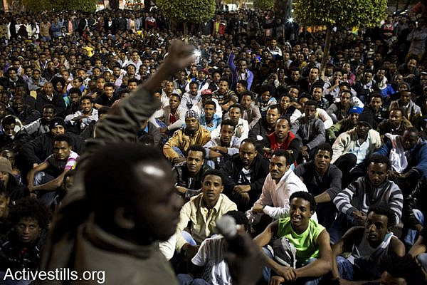 African asylum seekers gather in Levinsky Park before a March For Freedom, protesting against Holot detention centre located in Israel's south and the release of all refugees imprisoned under the Infiltrators Law, Tel Aviv, Israel, December 28, 2013. More than 5000 thousands African refugees participated in the march, supported by a few hundred Israeli activists, all calling for recognition of all refugees rights. (Oren Ziv/Activestills.org)