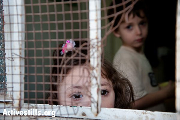 The children of Hashem Al Azzeh look through a window in their house near the Israeli settlement of Tel Rumeida in the West Bank city of Hebron. Their home has been attacked by Israeli settlers on numerous occasions. (Activestills)