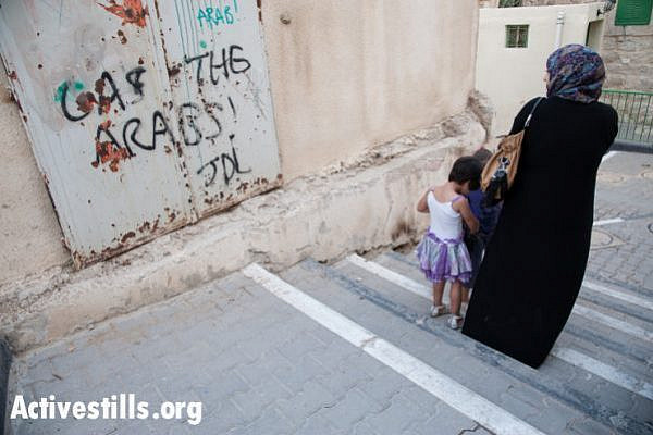 "A Palestinian woman and children pass the slogan ""Gas the Arabs! JDL"" spray-painted on an exterior wall of the Cordoba School for Palestinian children near Shuhada Street, Hebron, October 22, 2012. ""JDL"" stands for Jewish Defense League, an extremist group founded by Meir Kahane and designated as a terrorist group by the FBI. Baruch Goldstein was a charter member of the JDL, which has designated him ""a martyr in Judaism's protracted struggle against Arab terrorism."""
