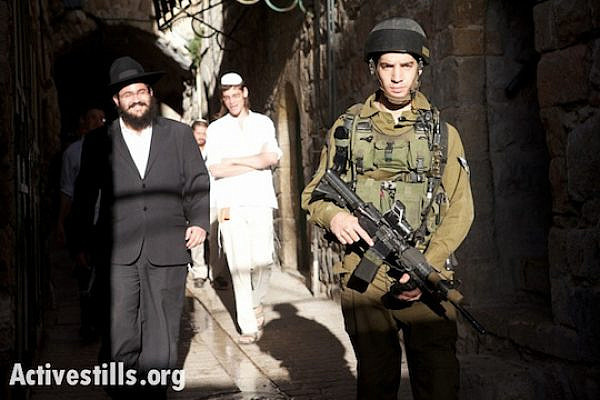An Israeli soldier escorts a group of settlers during a tour of Hebron's old city, February 20, 2010. (Photo by Activestills.org)