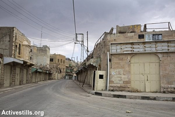 Shuhada Street in the Old City of Hebron, empty of all Palestinian vehicle and pedestrian traffic, November 13, 2013. Shuhada Street was the main commercial center of the city when it was first closed in 1994 to Palestinian traffic after the Ibrahimi Mosque Massacre, and later to pedestrians as the army shut down the entire commercial area. (Photo: Keren Manor/Activestills.org)