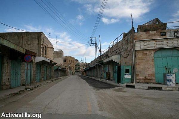 Shuttered shops on Hebron's Shuhada Street. (Photo by Keren Manor/Activestills.org)