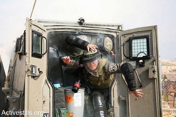 Israeli border policemen jump out of their jeep after a tear grande exploded unintentionally inside it as they were trying to disperse the weekly protest against the Israeli wall in the West Bank village of Bilin, February 7, 2014. (photo: Hamde Abu Rahma/Activestills.org)