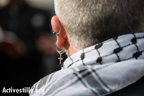 An international activist wears a traditional Palestinian keffiyeh and a cross earring while attending the Christ at the Checkpoint conference in the West Bank town of Bethlehem, March 14, 2014. The conference was organized by Palestinian Christians to educate the global church about the reality of injustice faced by those living under occupation and to study what the teachings of Jesus have to say about peace and justice in Palestine and Israel. (photo: Ryan Rodrick Beiler/Activestills.org)