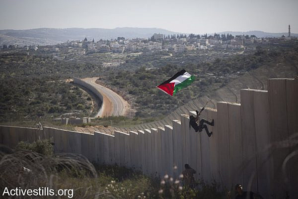 A Palestinian youth places a flag on the Israeli wall during a protest marking 9 years for the struggle against the wall in the West Bank village of Bilin, February 28, 2014. (photo: Oren Ziv/Activestills.org)