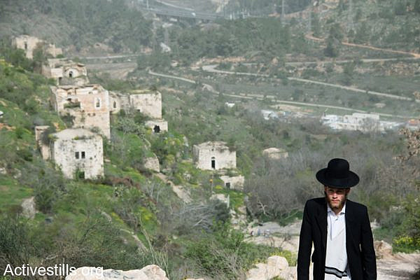 An ultra-orthodox Jewish man walks in the depopulated Palestinian village of Lifta, located on the edge of West Jerusalem, Israel, March 4, 2014. During the Nakba, the residents of Lifta fled attacks by Zionist militias beginning in December 1947, resulting in the complete evacuation of the village by February 1948. (photo: Ryan Rodrick Beiler/Activestills.org)