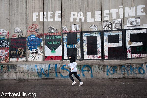 """A young woman runs next to the Israeli separation wall as hundreds of Palestinian and international athletes took part in the the inaugural Palestine Marathon which took place in Bethlehem, West Bank, April 21, 2013. Under the title """"Right to Movement"""" runners had to complete two laps of the same route, as organizers were unable to find a single course of 42 uninterrupted kilometers under Palestinian Authority control."""