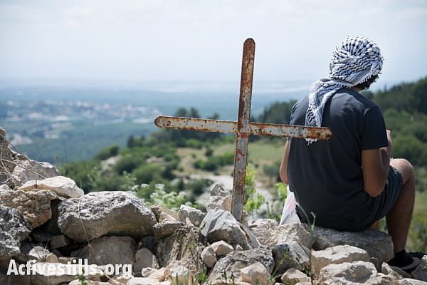 A youth sits near a cross overlooking the surrounding countryside in the displaced Palestinian village of Iqrit in northern Israel, April 21, 2014. Iqrit's original inhabitants were forcibly evacuated in the Nakba of 1948. Though the Israeli high court granted the residents, who are Palestinian citizens of Israel, the right to return to their homes in 1951, the military destroyed the village and has since prevented their return. Only the village's church and cemetery remained intact, and are still used by village residents while they campaign for a full return.