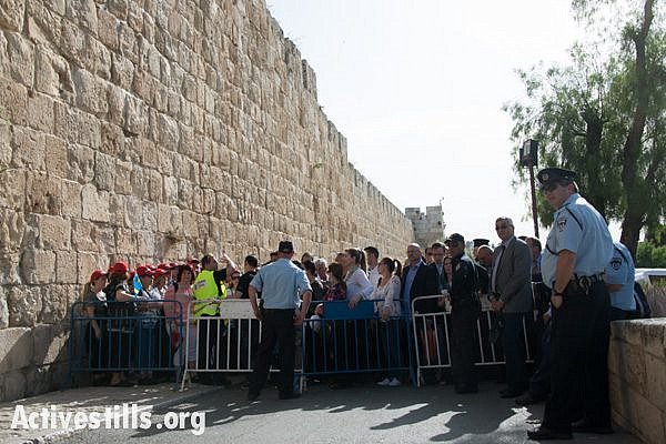 """An Israeli police checkpoint blocks access to the Old City of Jerusalem, April 19, 2014. The day before Easter, thousands of Palestinian Christians and international pilgrims attempt to enter Jerusalem's Old CIty to participate in the """"Saturday of Light"""" or """"Holy Fire"""" celebration in the Church of the Holy Sepulcher, the traditional site of the crucifixion, burial and resurrection of Jesus. (photo: Ryan Rodrick Beiler/Activestills.org)"""