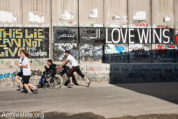 "A Palestinian runner pushes a friend in a wheelchair along the Israeli separation wall dividing the West Bank town of Bethlehem during the second annual Palestine Marathon, April 11, 2014. Some 2,500 Palestinian and 700 international runners participated in 5K, 10K, half marathon and full marathon races under the title ""Right to Movement"". Full marathon runners had to complete two laps of the same route, as organizers were unable to find a single course of 42 uninterrupted kilometers under Palestinian Authority control."