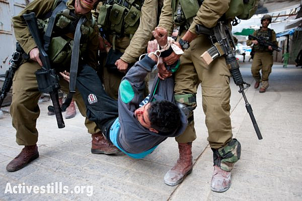Israeli soldiers arrest a Palestinian youth, who shows signs of being beaten, following a demonstration in the West Bank city of Hebron, March 1, 2013. (photo: Activestills.org)