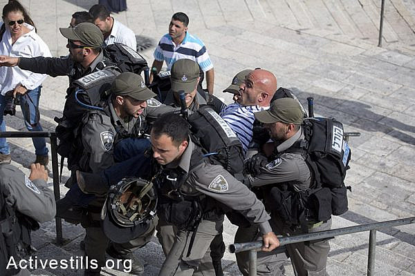 Israeli border policemen detain a Palestinian journalist before Israeli settlers and Ultra-nationalists take part in the 'flag march' through Damascus Gate in east Jerusalem, on May 28, 2014, celebrating the anniversary of its capture in the 1967 Six-Day War. Police prevented from Palestinians to gather and  protest against the march, and attacked journalists that were covering  the event. (Oren Ziv/Activestillsorg)