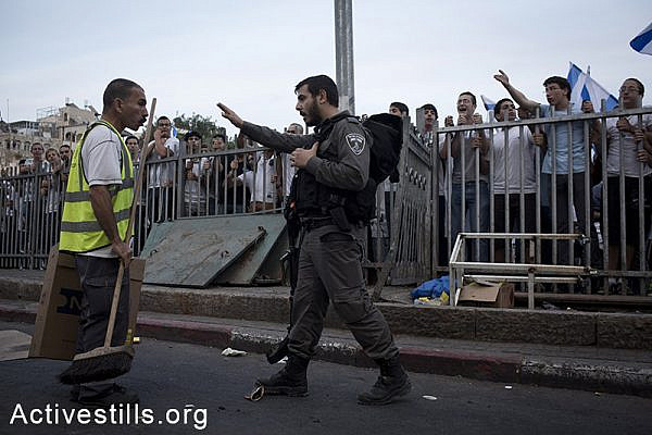 A Palestinian cleaning worker argues with Israeli settlers as during a protest against the 'flag march', in which Israeli settlers and Ultra-nationalists march through Damascus Gate in East Jerusalem, on May 28, 2014, celebrating the anniversary of its capture in the 1967 Six-Day War.