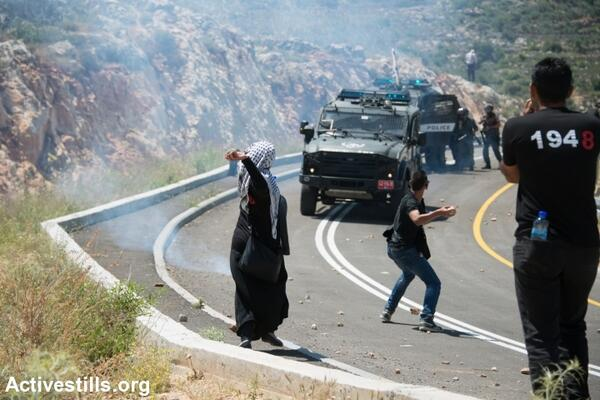 Palestinians throw stones at an Israeli military jeep during a Nakba Day protest in the village of Al-Walaja. (photo: Activestills.org)