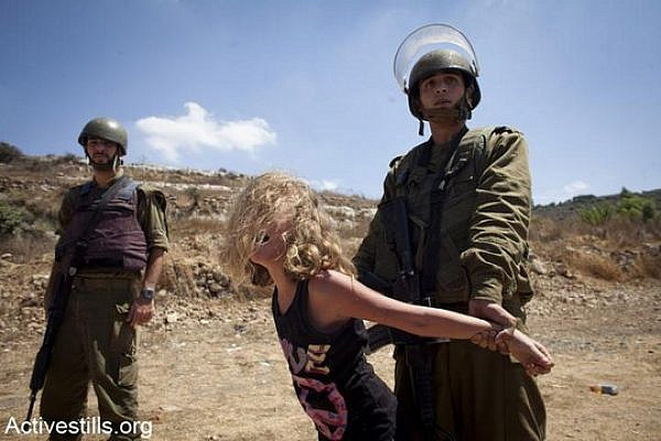 Illustrative photo of a young Palestinian girl being detained by Israeli soldiers. (Photo by Activestills.org)