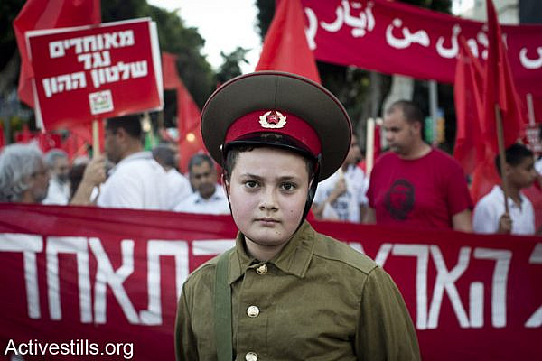 A youth dressed with uniform of the USSR army, marches during a protest marking the International Worker's Day in center Tel Aviv, May 1, 2014.