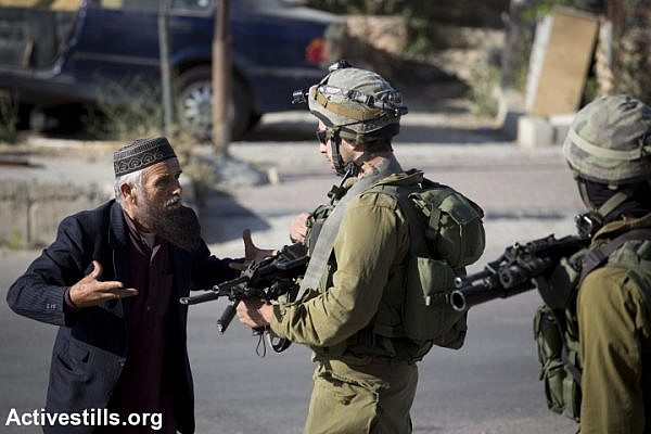 An elderly Palestinian man argues with an Israeli soldier taking part in the search operation for three Israeli teenagers believed to have been kidnapped by Palestinian militants, on June 17, 2014 in the West Bank city of Hebron. Israel stepped up efforts against Hamas in the West Bank Tuesday as the hunt for three Israeli teenagers entered its fifth day. (Photo: Oren Ziv/Activestills.org)