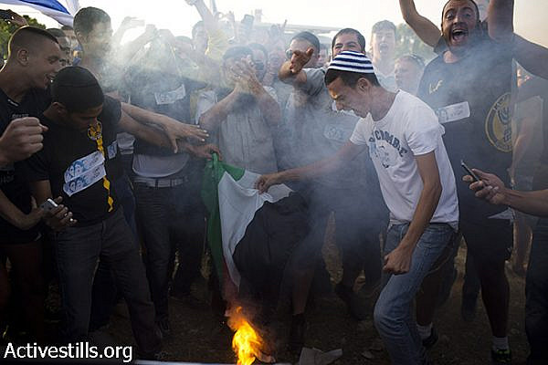 Right wing Israelis burn a Palestinian flag and shout racist slogans during an anti-Palestinian demonstration at the Gush Etzion junction, a settlement next to the Palestinian town of Bethlehem ,on June 16, 2014. (Oren Ziv/Activestills.org)