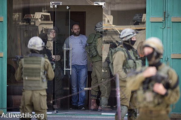 Israeli soldiers from a special army unit take part in a search operation raid a Palestinian shop in the West Bank town of Hebron. June 18, 2014 (Oren Ziv/Activestills.org)