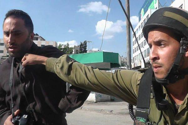 IDF soldier punching Issa Amro in Hebron (photo: Awni Abu Shamsieh)