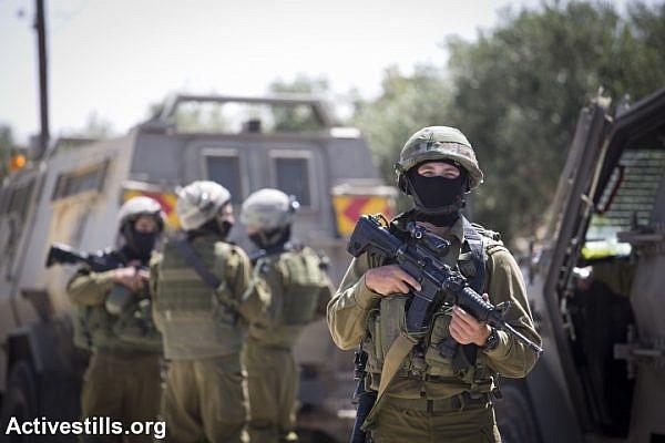 Israeli soldiers raid the city of Halhul, near Hebron. (photo: Activestills)