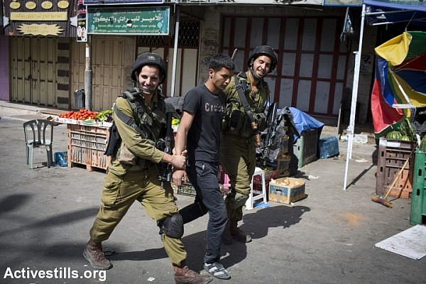 Israeli soldiers smile as they arrest a Palestinian man in Hebron. The army has put the city under closure while it searches for three kidnapped teenagers. (photo: Activestills.org)