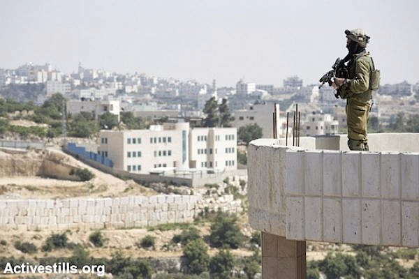 An Israeli soldier stands on the rooftop of a Palestinian home in the West Bank city of Hebron, June 18, 2014. (File photo by Oren Ziv/Activestills.org)