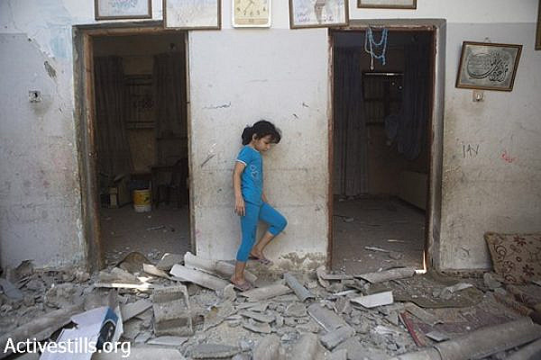 A child of Diab Bakr is seen amidst the rubble of his home which was destroyed last night by Israeli missiles, in As-Shati refugee camp, Gaza city, July 22, 2014. Another home from the extended Bakr family was also destroyed and another one damaged. Hassan Khader Bakr, was killed during the attack in the street. Their cousins, Bakr family who live in the same area, lost four children, Ahed (10), Zacharia (10), Mohamed (9) after they were targeted by two Israeli missiles while playing at the beach on 16 July, 2014. (Anne Paq/Activestills.org)