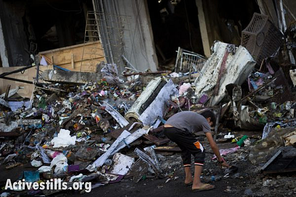 A child inspects the ruins of a house destroyed by an Israeli air strike in the Al Sheikh Radwan neighborhood of Gaza City, July 11, 2014.