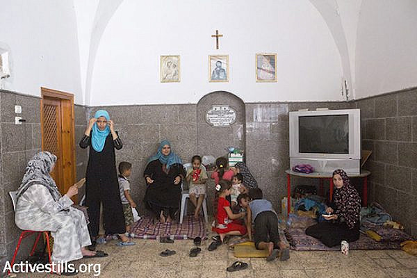 Palestinians sit inside central Gaza City's Church of St. Porphyrius where they find refuge, July 22, 2014. (Anne Paq/Activestills.org)