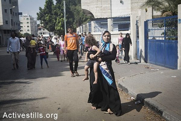 Gazans flee the Shejaiya area after Israeli tanks invaded the area, bombarding it heavily, causing over 60 casualties and hundreds wounded, July 20, 2014.  (Basel Yazouri/Activestills.org)