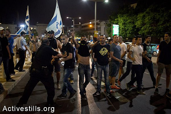 Right-wing nationalists attacking left-wing activists during a protest in central Tel Aviv against the Israeli attack on Gaza, July 12, 2014. The protest ended with the nationalists attacking a small group of left-wing activists, with little police interference. Three activists were injured and one right-wing person was arrested. (Oren Ziv/Activestills.org)