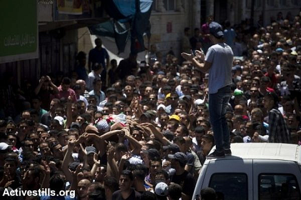 Mourners carry the body of killed Palestinian Mohammed al-Araj during his funeral at the Qalandiya Palestinian refugee camp near the West Bank city of Ramallah, on July 25, 2014, after he was shot and killed the night before during clashes with the Israeli army amid a massive protest in the West Bank against the Israeli attack on the Gaza strip. (photo: Activestills)