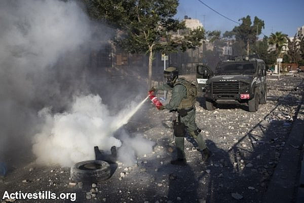 An Israeli Border Police officer puts out a fire as clashes subside following the funeral of Mohammed Abu Khdeir, Shuafat, East Jerusalem, July 4, 2014. (Photo by Oren Ziv/Activestills.org)