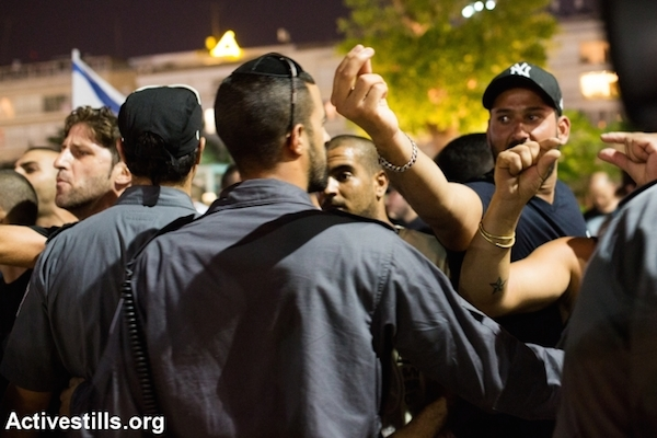 Police stopping right-wing nationalists from attacking left wing activists during a protest in central Tel Aviv against the Israeli attack on Gaza, July 12, 2014. The protest ended with the nationalists attacking a small group of left-wing activists with little police interference. (Photo by Yotam Ronen/Activestills.org)