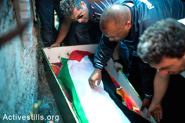 Palestinian residents of Shuafat stand above the body of Muhammad Abu Khdeir during his funeral. (photo: Activestills)