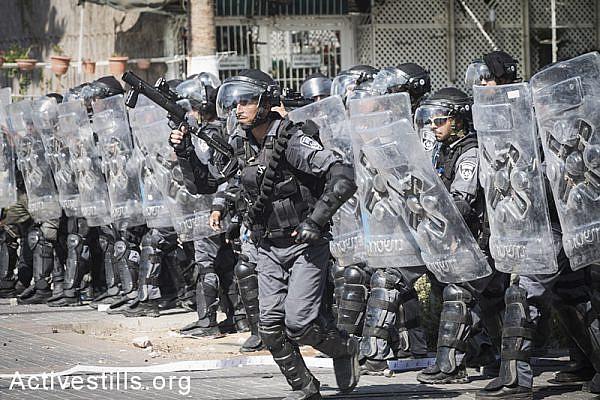 Israeli riot policemen shoot tear gas at Palestinians in Shuafat during the funeral of Muhammad Abu Khdeir. (photo: Oren Ziv/Activestills.org)