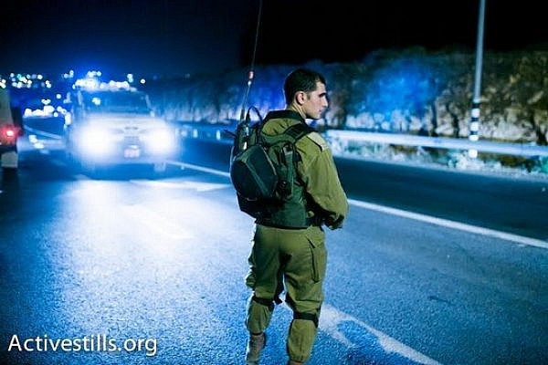 Israeli army officer next to the site where the bodies of three missing teens were located, June 30 2014 (photo: Activestills)