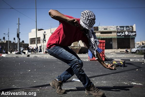 A Palestinian uses a slingshot to throw rocks at Israeli forces in Shuafat refugee camp. Clashes erupted after the body of a Palestinian teenager was found in a Jerusalem forest. (photo: Activestills.org)