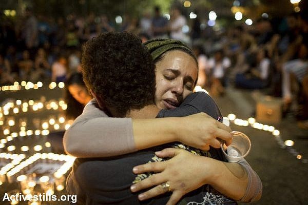 Israeli mourners console each other during a memorial for the three murdered teens in Rabin Square, Tel Aviv. (photo: Activestills)