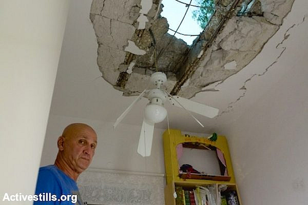 An Israeli looks at damage to his home in a kibbutz near border with the Gaza Strip on Wednesday, July 9, 2014. (Photo by Yotam Ronen/Activestills.org)