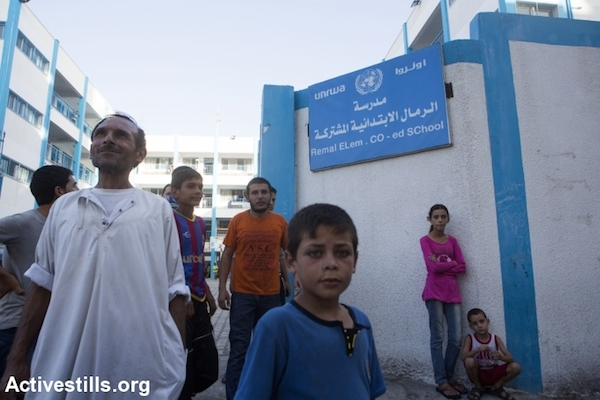 Palestinians stand in front of the entrance of Remal Elementary UNRWA School which is used as a temporary shelter for people from the northern part of the Gaza Strip, Gaza City on July 13, 2014. People from northern Gaza left their homes after Israel dropped leaflets warning them to evacuate. Israeli attacks have killed at least 166 Palestinians, including 30 children. (Photo by Anne Paq/Activestills.org)