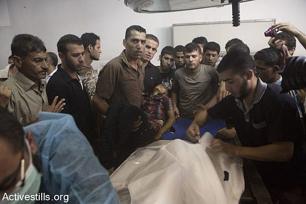 Palestinians gather around a child killed earlier in a playground in al-Shati refugee camp at the morgue of Al-Shifa hospital, Gaza city, July 28, 2014. Reports indicate that 10 people, mostly children, were killed and 40 injured during the attack which took place on the first day Eid.  (Anne Paq/Activestills.org)
