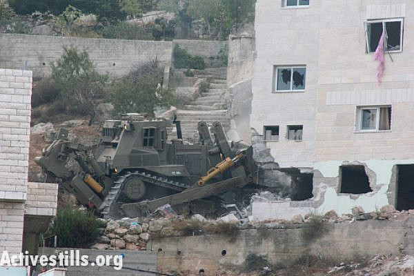An Israeli military bulldozer destroys part of the family home of Zakaria Al-Aqra, age 24, after he was killed by an army raid in the West Bank village of Qabalan, August 11, 2014.